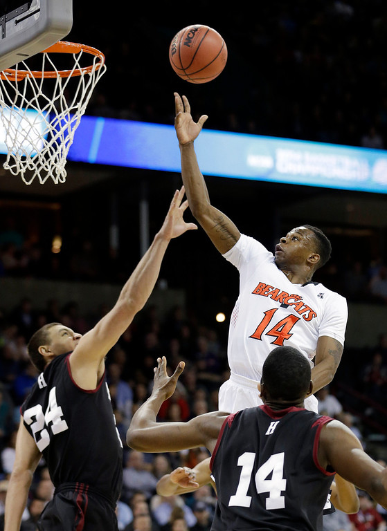 . Cincinnati\'s Ge\'Lawn Guyn (14) puts up a shot over Harvard\'s Jonah Travis (24) and Steve Moundou-Missi during the first half of a second-round game of the NCAA college basketball tournament in Spokane, Wash., Thursday, March 20, 2014. (AP Photo/Elaine Thompson)