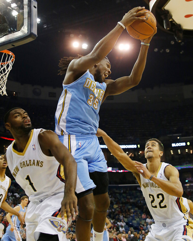 . Denver Nuggets power forward Kenneth Faried (35) grabs a rebound in front of New Orleans Pelicans small forward Tyreke Evans (1) and point guard Brian Roberts (22) in the first half of an NBA basketball game in New Orleans, Sunday, March 9, 2014. (AP Photo/Bill Haber)