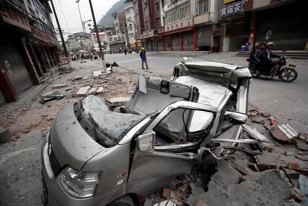. Residents ride on a motorcycle past a damaged car on a street after Saturday\'s earthquake in Lingguan town of Baoxing county, Sichuan province April 21, 2013REUTERS/Suzie Wong