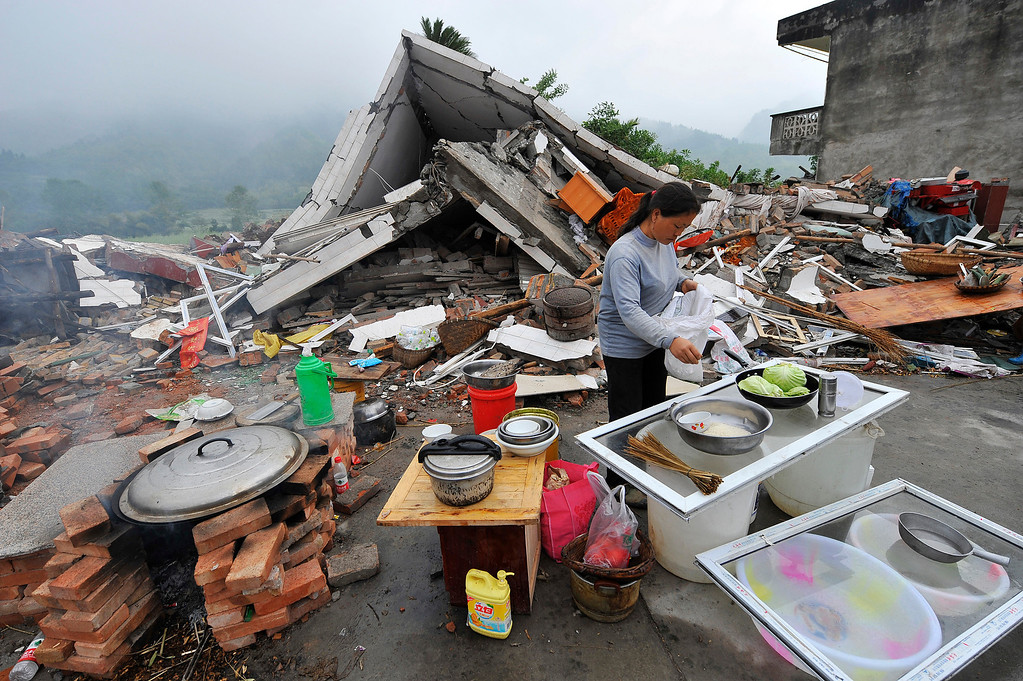 . This photo taken on April 23, 2013 shows a woman cooking beside collapsed houses in Lushan county of Yaan, southwest China\'s Sichuan province. Tens of thousands of homeless survivors of China\'s devastating quake are living in makeshift tents or on the streets, facing shortages of food and supplies as well as an uncertain future. AFP/Getty Images