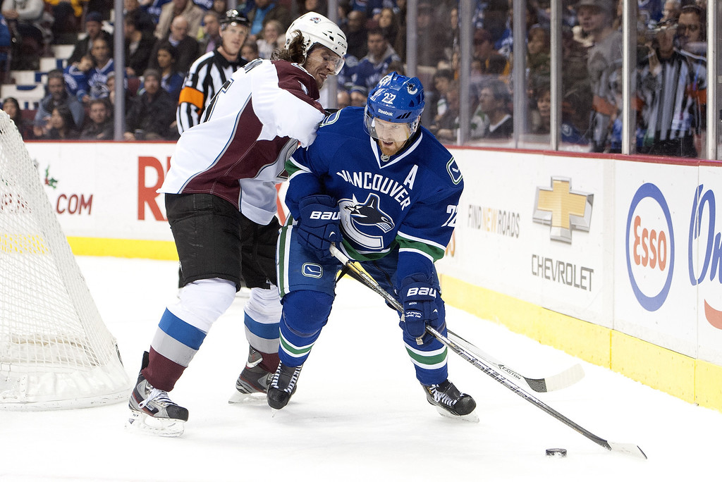 . Daniel Sedin #22 of the Vancouver Canucks fights off the check of Nate Guenin #5 of the Colorado Avalanche during the second period in NHL action on December 08, 2013 at Rogers Arena in Vancouver, British Columbia, Canada.  (Photo by Rich Lam/Getty Images)