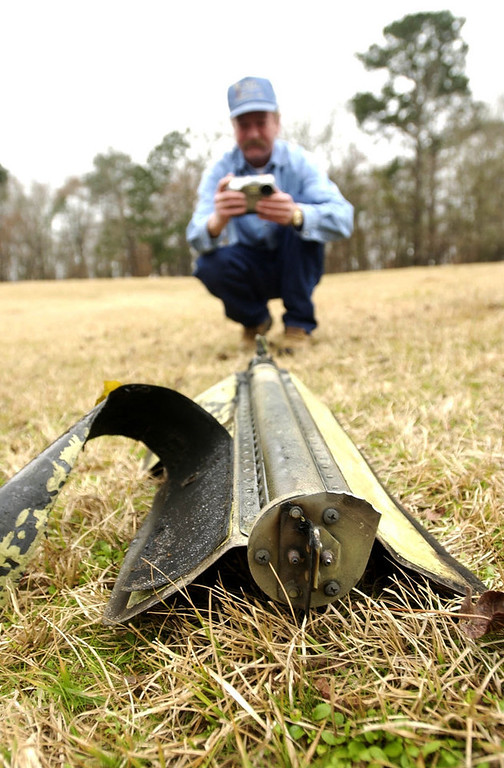 . John Mast of Nacogdoches takes a picture of a piece of what is believed to be debris of the Columbia space shuttle at his Farm in Melrose, TX. on Monday. (The Denver Post/ Hyoung Chang)