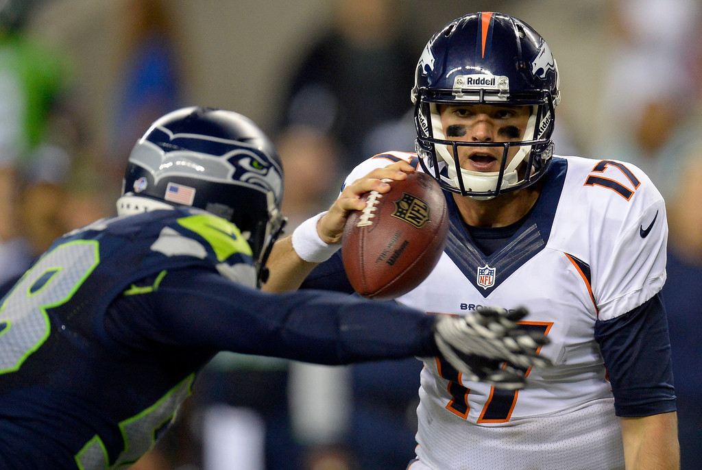 . SEATTLE, WA. - AUGUST 17: Denver Broncos quarterback Brock Osweiler (17) scrambles from Seattle Seahawks linebacker Ty Powell (58) during the fourth quarter  August 17, 2013 at Century Link Field. (Photo By John Leyba/The Denver Post)