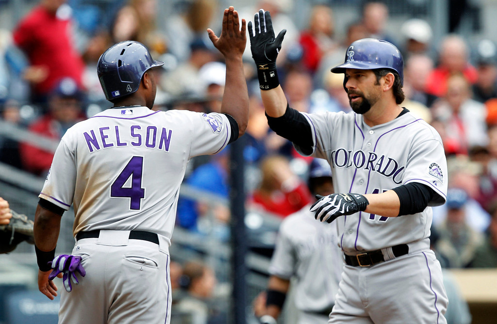 . Colorado Rockies\' Chris Nelson (4) congratulates Todd Helton, right, on his pinch-hit, two-run home run against the San Diego Padres in the seventh inning during a baseball game, Sunday, April 14, 2013, in San Diego. (AP Photo/Alex Gallardo)