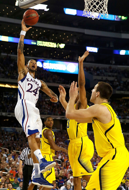 . Kansas Jayhawks guard Travis Releford (L) shoots over Michigan Wolverines forward Mitch McGary (R) during the first half in their South Regional NCAA men\'s basketball game in Arlington, Texas March 29, 2013. REUTERS/Jim Young