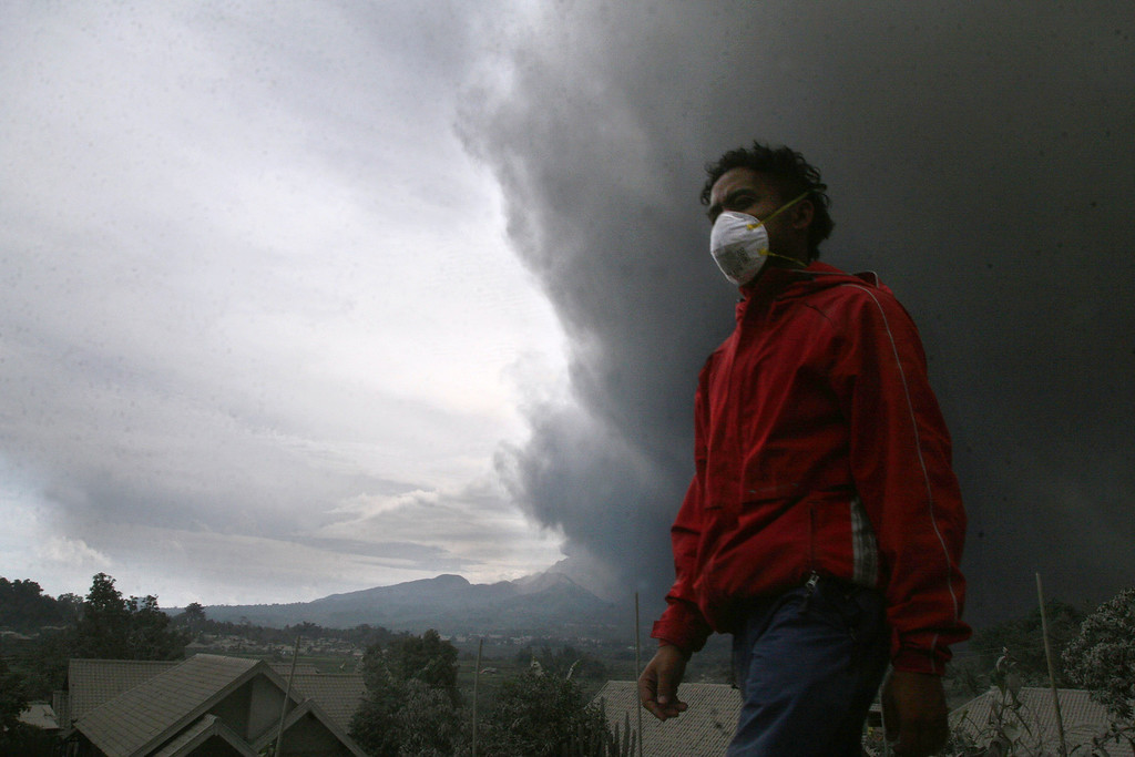 . A resident evacuates under a massive plume of hot ash clouds spewing from Mount Kelud volcano as seen from Malang district in East Java province on February 14, 2014.  AFP PHOTO / AMAN ROCHMAN/AFP/Getty Images