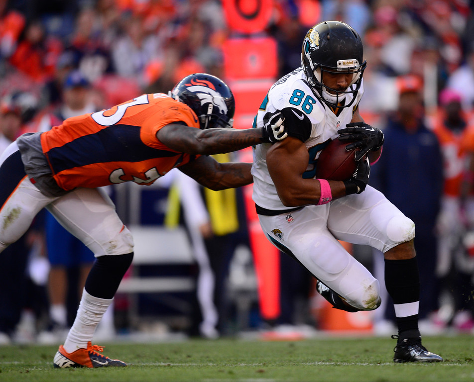 . Denver Broncos strong safety Duke Ihenacho (33) tries to tackle Jacksonville Jaguars tight end Clay Harbor (86) in the third quarter.  (Photo by AAron Ontiveroz/The Denver Post)