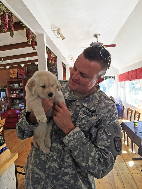 . Major David Gibb of the Utah Army National Guard with Chinook the puppy at the Colorado Cherry Company in Pinewood Springs. (Photo by Laura Levy)