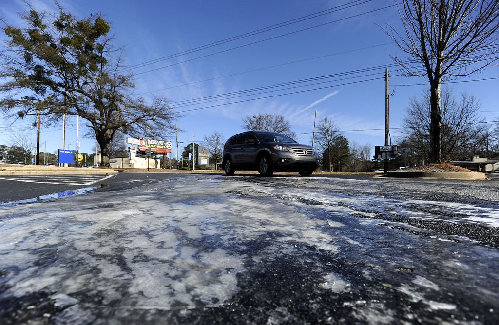 . A driver negotiates an ice patch in a parking lot as a cold Arctic blast brought temperatures down to 6 degrees above zero to shatter cold weather records, on Tuesday, Jan. 7, 2014, in Atlanta. (AP Photo/David Tulis)