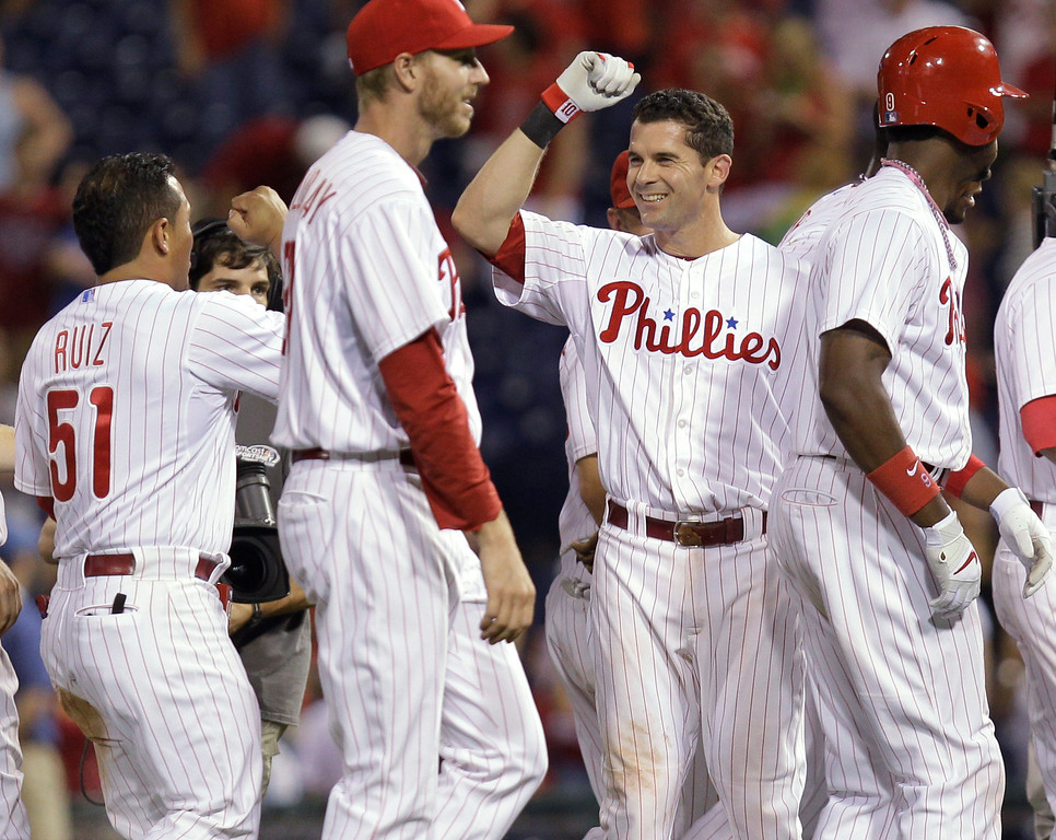 . Philadelphia Phillies\' Michael Young, center, celebrates with Carlos Ruiz and other teammates after his game-winning hit in the ninth inning against the Colorado Rockies in a baseball game, Wednesday, Aug. 21, 2013, in Philadelphia. The Phillies won 4-3. (AP Photo/Laurence Kesterson)