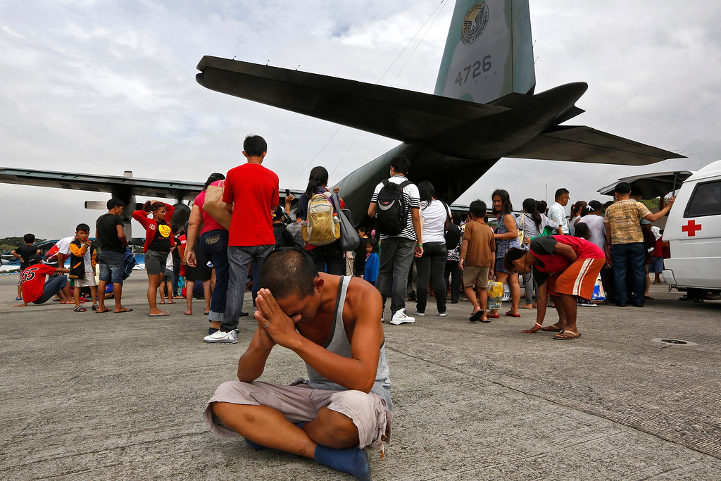 . A survivor from Tacloban, which was devastated by Typhoon Haiyan gestures while sitting on the ground after disembarking a Philippine Air Force C-130 aircraft at the Villamor Airbase, Tuesday, Nov. 12, 2013, in Manila, Philippines.  Authorities said at least 9.7 million people in 41 provinces were affected by the typhoon, known as Haiyan elsewhere in Asia but called Yolanda in the Philippines. It was likely the deadliest natural disaster to beset this poor Southeast Asian nation. (AP Photo/Vincent Yu)