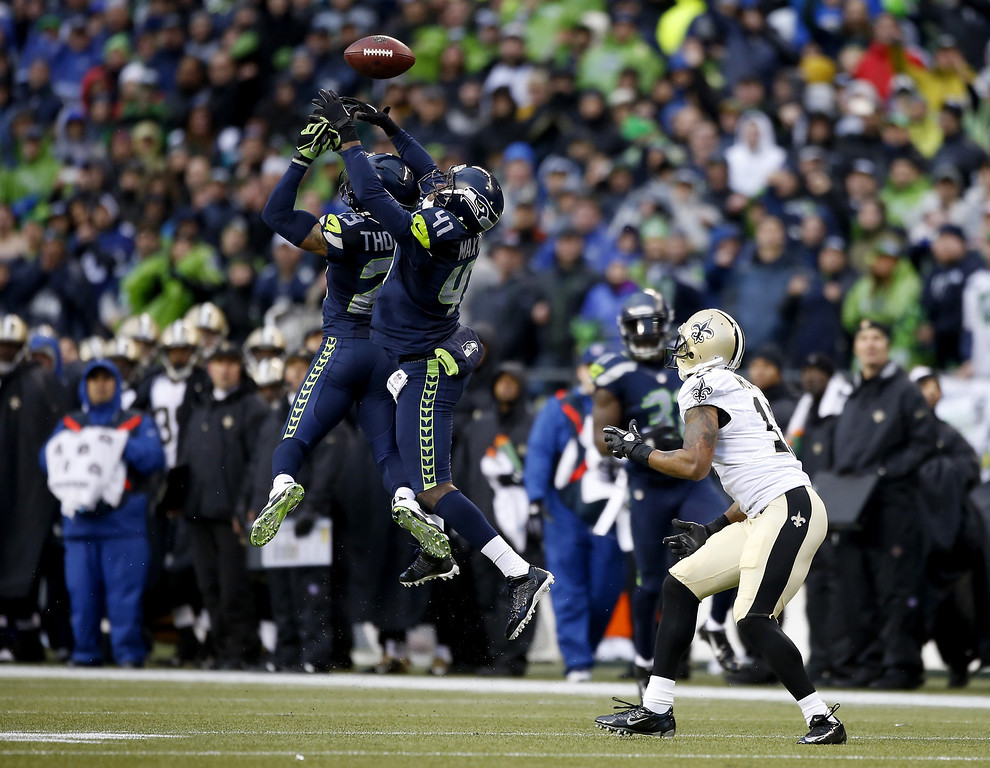 . SEATTLE, WA - JANUARY 11:  Cornerback Byron Maxwell #41 and free safety Earl Thomas #29 of the Seattle Seahawks are unable to make an interception as the ball is caught by wide receiver Robert Meachem #17 of the New Orleans Saints in the fourth quarter during the NFC Divisional Playoff Game at CenturyLink Field on January 11, 2014 in Seattle, Washington.  (Photo by Otto Greule Jr/Getty Images)