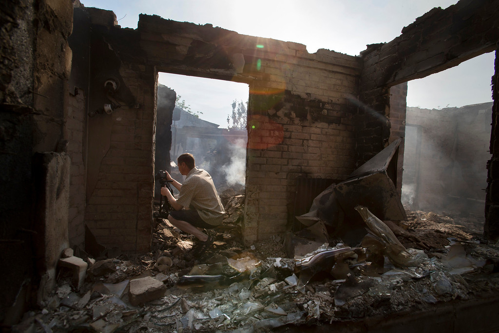 . A journalist films a destroyed house following a mortar attack in Semyonovka village, outside Slovyansk, Ukraine, Friday, May 23, 2014. The village on the outskirts of Slovyansk, a city which has been the epicenter of clashes for weeks, has seen continuous shelling by the Ukrainian government forces, who have retaliated to the rebel fire. On Friday, the private house was destroyed by mortar fire that came from the Ukrainian side. There were no casualties, as the family living there had left the previous day, according to local residents. (AP Photo/Alexander Zemlianichenko)