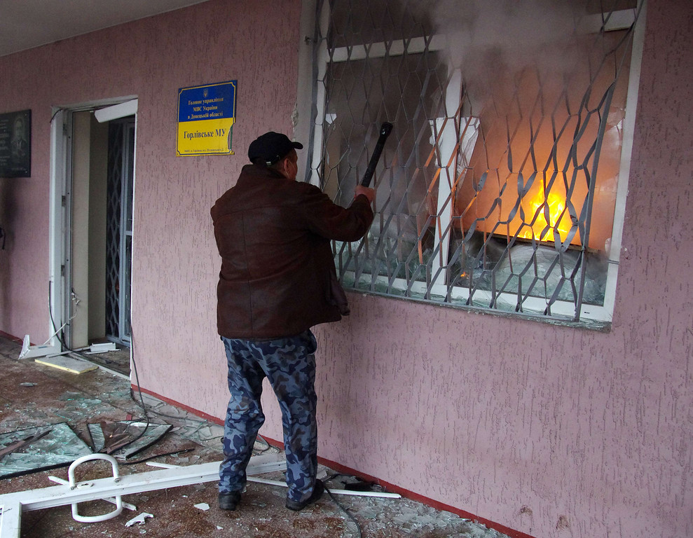 . A pro-Russia protester breaks a window of a regional police building in the eastern Ukrainian city of Horlivka (Gorlovka), near Donetsk, on April 14, 2014. A few hundred pro-Russia activists seized the building after an hour-long storming. Ukraine\'s interim president on April 14 made a dramatic about-face aimed at defusing tensions in the separatist east by backing a national referendum on turning the ex-Soviet republic into a federation with broader regional rights.   AFP PHOTO/ ALEXEY  KRAVTSOV/AFP/Getty Images