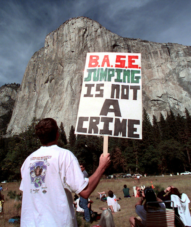 """. A protestor holds a sign in front of El Capitan in Yosemite, Calif., National Park before skydiver Jan Davis, 60, died after attempting to parachute Friday, Oct. 22, 1999. The skydivers jumped in a protest against the policy of skydiving in Yosemite. The organization \""""It\'s Our Park Too!\"""" and the National Park Service worked out an agreement for several skydivers to jump.   (AP Photo/Paul Sakuma)"""