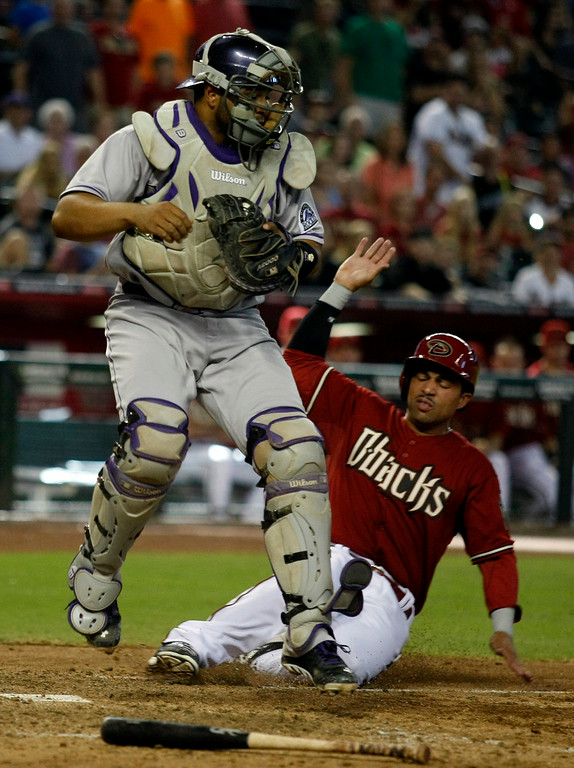 . Colorado Rockies catcher Wilin Rosario , left, gets the force-out while avoiding Arizona Diamondbacks\' Xavier Paul, right,in the ninth inning during a baseball game, Sunday, Aug. 10, 2014, in Phoenix. (AP Photo/Rick Scuteri)