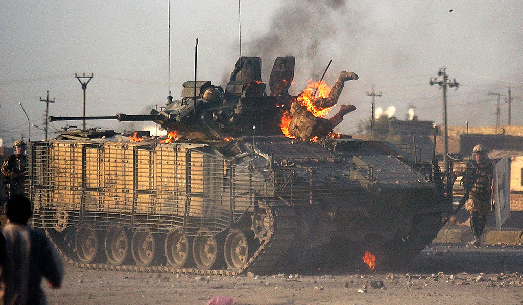 . A British soldier makes his way out of a burning Warrior fighting vehicle in Basra, 550 kilometers (340 miles) southeast of Baghdad Monday Sept. 19, 2005. British forces and demonstrators exchanged gunfire in the southern city of Basra leaving two civilians dead after two British men were arrested for allegedly gunning down an Iraqi police officer, authorities and witnesses said Monday. Additional information on the status of the soldier emerging from the tank is unavailable. (AP Photo/Nabil al-Jurani)
