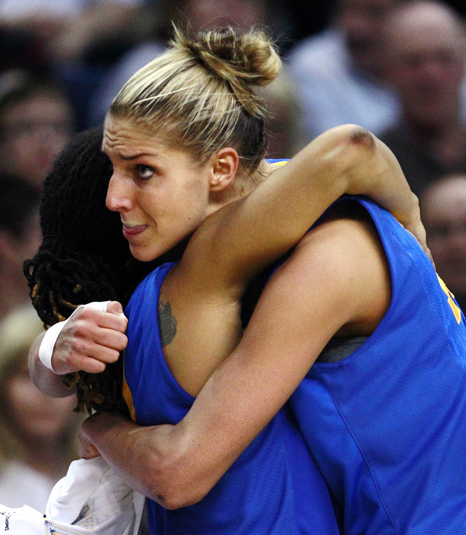. Delaware forward Elena Delle Donne, right, is embraced by Trumae Lucas in the final seconds of a regional semifinal in the NCAA college basketball tournament in Bridgeport, Conn., Saturday, March 30, 2013. Delle Donne scored 33 points, but Kentucky won 69-62. (AP Photo/Charles Krupa)
