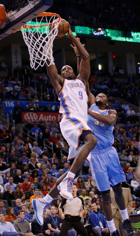 . Oklahoma City Thunder forward Serge Ibaka (L) of Congo, flies in for a dunk against Denver Nuggets forward Kenneth Faried in the second half of their NBA basketball game in Oklahoma City, Oklahoma January 16, 2013. REUTERS/Bill Waugh