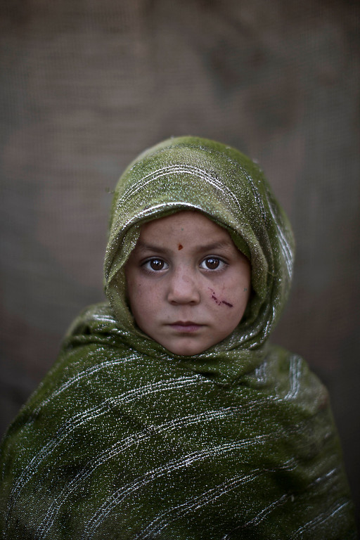 . In this Monday, Jan. 27, 2014 photo, Afghan refugee girl, Madina Juma\'a, 4, poses for a picture, while playing with other children in a slum on the outskirts of Islamabad, Pakistan. For more than three decades, Pakistan has been home to one of the world�s largest refugee communities: hundreds of thousands of Afghans who have fled the repeated wars and fighting their country has undergone. Since the 2002 U.S.-led invasion of Afghanistan, some 3.8 million Afghans have returned to their home country, according to the U.N.�s refugee agency. (AP Photo/Muhammed Muheisen)
