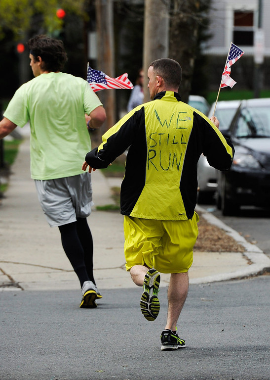 . Eric Wayne (R) and Mike Coppola run by Franklin Street with American flags on April 20, 2013 in Watertown, Massachusetts. A manhunt for Dzhokhar A. Tsarnaev, 19, a suspect in the Boston Marathon bombing ended after he was apprehended on a boat parked on a residential property in Watertown, Massachusetts. His brother Tamerlan Tsarnaev, 26, the other suspect, was shot and killed after a car chase and shootout with police. The bombing, on April 15 at the finish line of the marathon, killed three people and wounded at least 170.  (Photo by Kevork Djansezian/Getty Images)