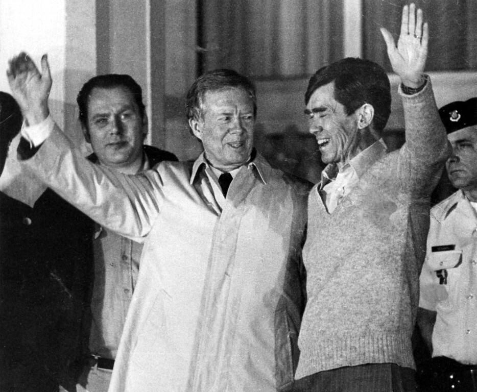 . Former US President Jimmy Carter, who had negotiated for the hostages release right up to the last hours of his Presidency, lifts his arm to the crowd, while putting his other hand around the shoulders of a former hostage in Iran, believed to be Bruce Laingen, at US AIR Force Hospital in Wiesbaden, Germany, Wednesday, January 21, 1981. The United States had agreed to unfreeze Iran\'s assets in exchange for the hostages freedom. (AP Photo/Mark Goecks)