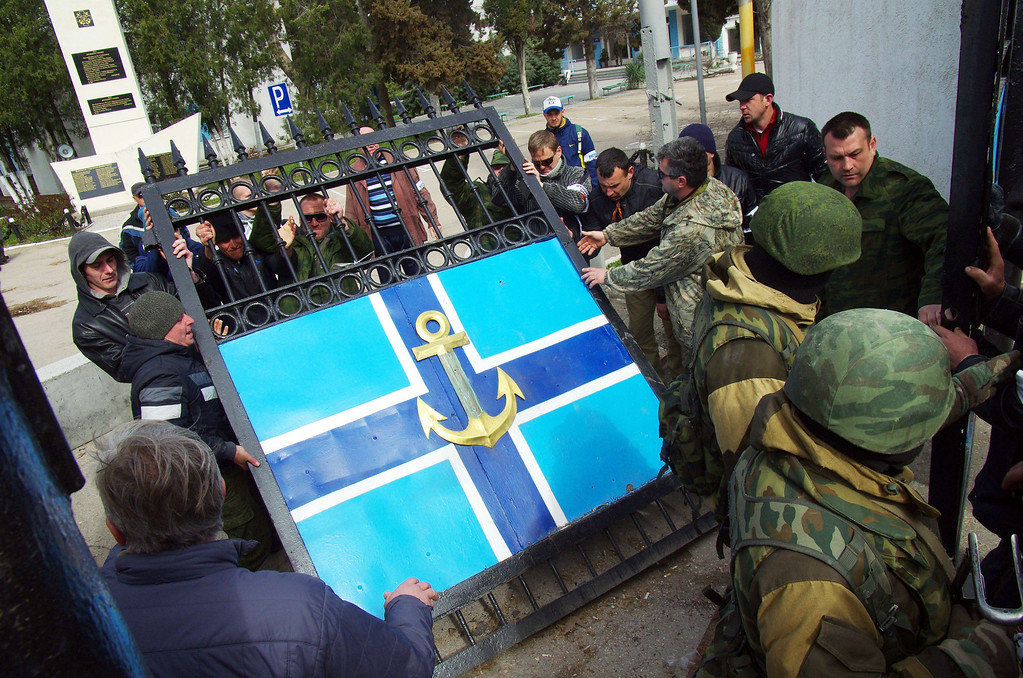 . Pro-Russian protesters remove the gate of Ukrainian navy headquarters as Russian troops stand guard in Crimean city of Sevastopol on March 19, 2014. Pro-Russian protesters seized Ukraine\'s Crimean naval headquarters and captured its commander on Wednesday after Moscow claimed the peninsula and the first casualties ratcheted up stakes in the worst East-West standoff since the Cold War.  AFP PHOTO/  VASILIY  BATANOV/AFP/Getty Images