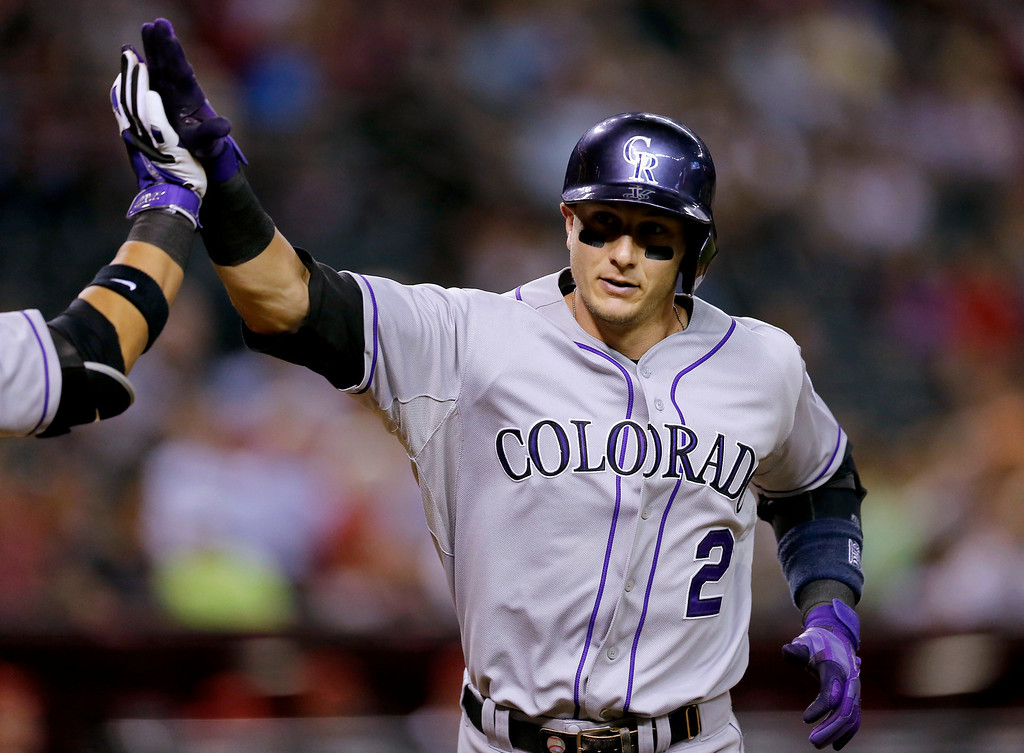 . Colorado Rockies\' Troy Tulowitzki, left, rounds the bases after hitting a solo home run against the Arizona Diamondbacks during the sixth inning of a baseball game on Monday, April 28, 2014, in Phoenix. (AP Photo/Matt York)