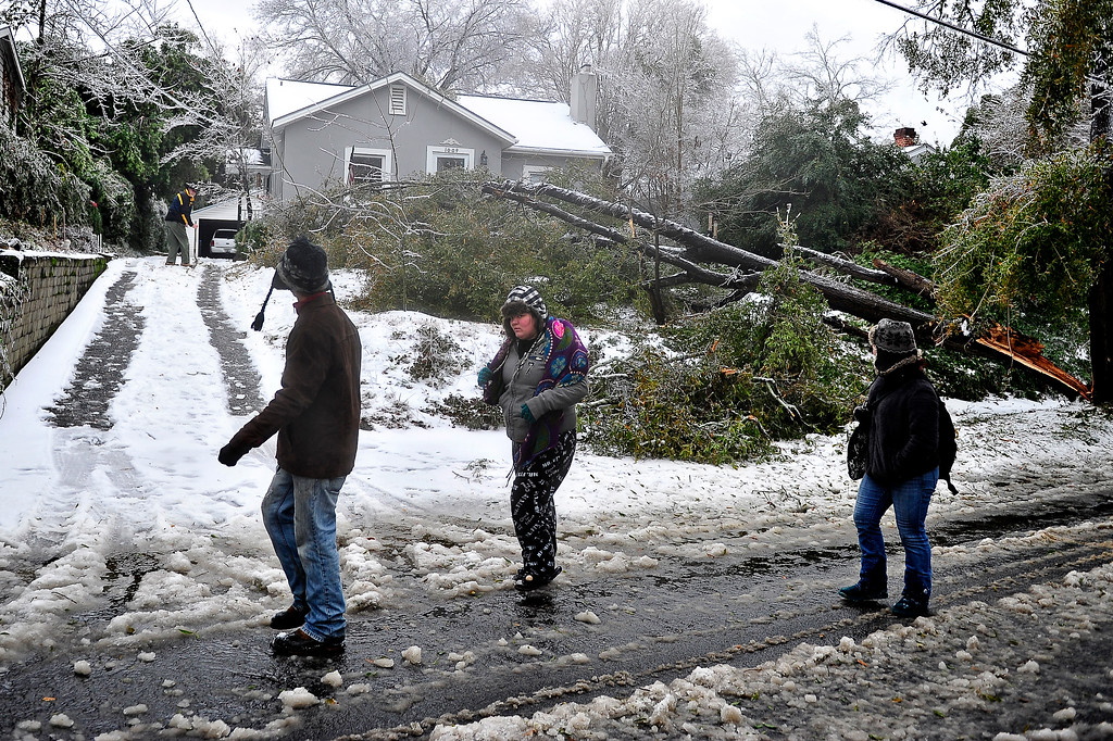 . Pedestrians walk past a tree that fell in the yard of a house on Baker Avenue, that narrowly missed the home, as a winter storm hit Augusta, Ga., Wednesday, Feb. 12, 2014. (AP Photo/The Augusta Chronicle, Jon-Michael Sullivan)