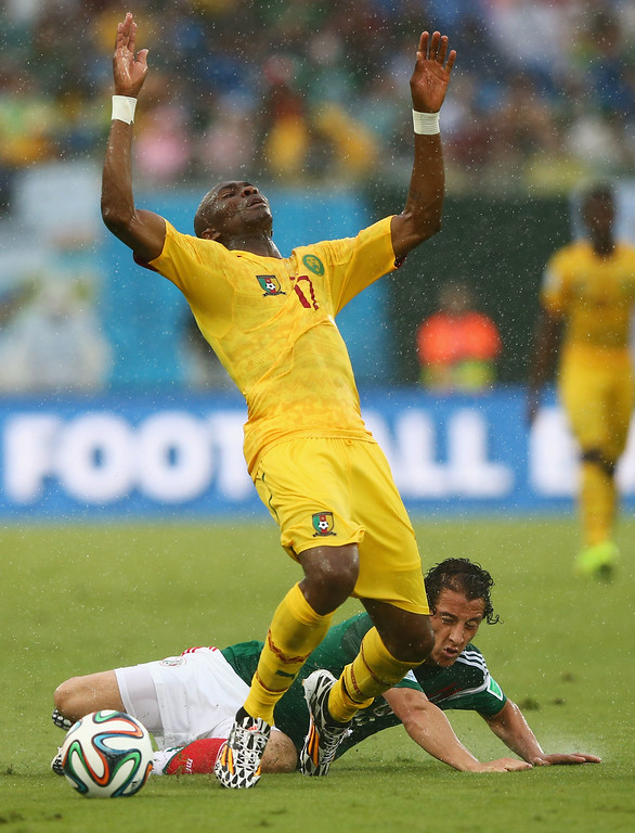 . Stephane Mbia of Cameroon reacts to a challenge by Andres Guardado of Mexico in the first half during the 2014 FIFA World Cup Brazil Group A match between Mexico and Cameroon at Estadio das Dunas on June 13, 2014 in Natal, Brazil.  (Photo by Jamie Squire/Getty Images)