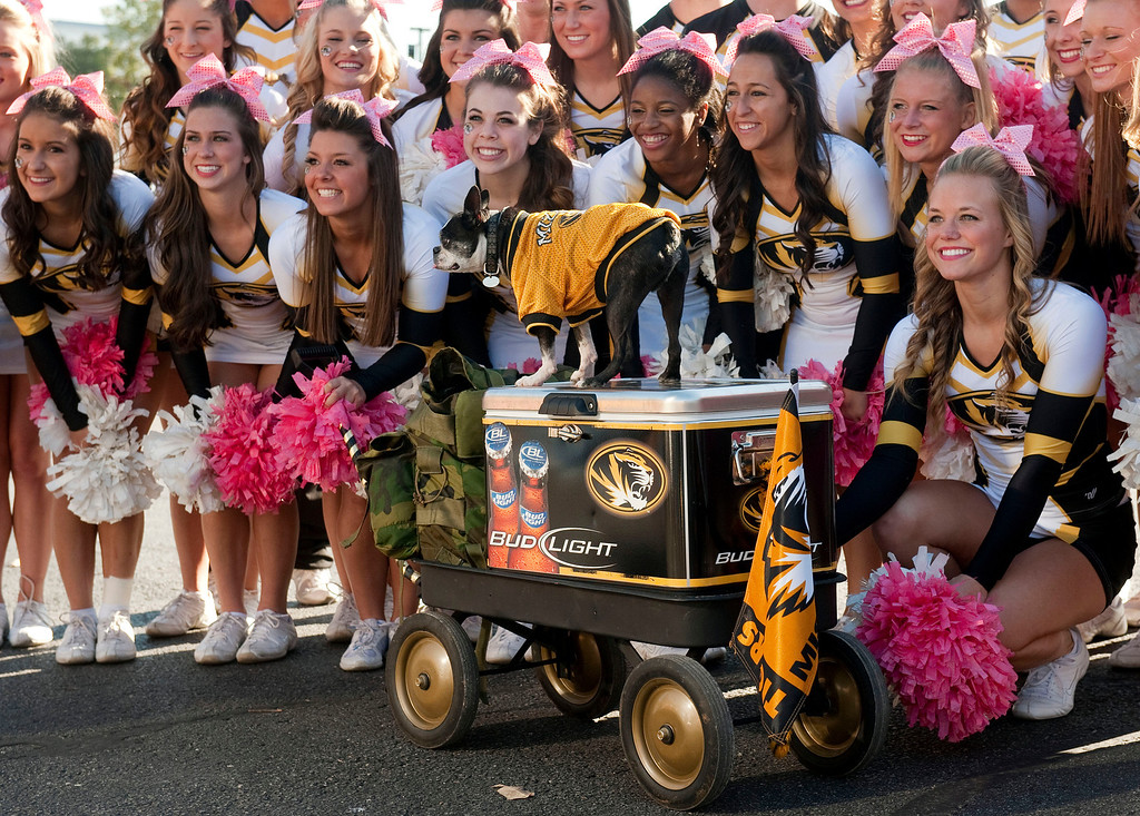 . The Missouri cheerleaders pose with Rommel the dog before the start of an NCAA college football game against South Carolina, Saturday, Oct. 26, 2013, in Columbia, Mo. (AP Photo/L.G. Patterson)
