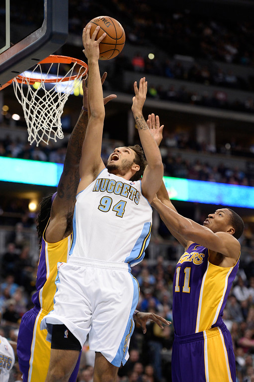 . DENVER, CO - NOVEMBER 13: Denver Nuggets shooting guard Evan Fournier (94) goes flies past ,l11 to the basket for a shot during the second quarter November 13, 2013 at Pepsi Center. (Photo by John Leyba/The Denver Post)