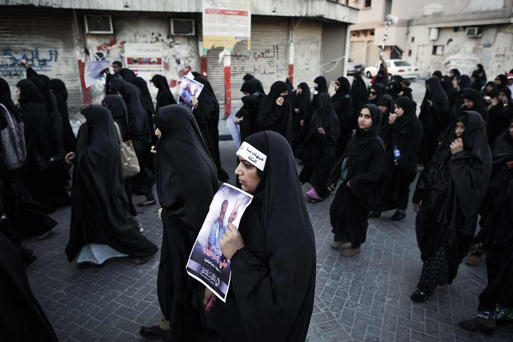 . Bahraini women carry placards during the funeral of 10-year-old Ali Jaffer Habib, in the village of Malikiya, on August 10, 2013. Habib, according to his family, died after developing cancer due to the inhalation of tear gas fired by security forces earlier in the year. MOHAMMED AL-SHAIKH/AFP/Getty Images