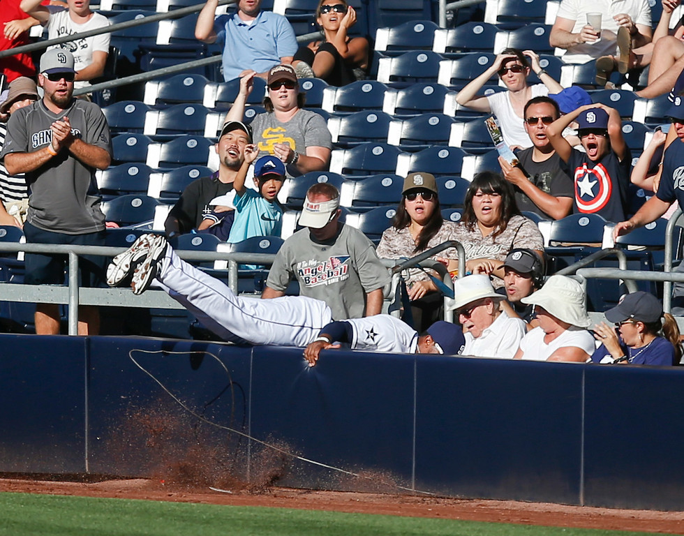 . San Diego Padres right fielder Rymer Liriano sails over the wall while trying to catch a pop foul hit by Colorado Rockies\' Michael McKenry as he runs into the wall in the fifth inning of a baseball game Wednesday, Aug. 13, 2014, in San Diego.  (AP Photo/Lenny Ignelzi)
