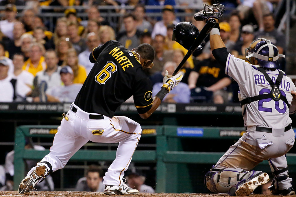 . Pittsburgh Pirates\' Starling Marte (6) recoils after being hit in the head by a pitch from Colorado Rockies reliever Adam Ottavino during the seventh inning of a baseball game in Pittsburgh on Friday, July 18, 2014. The tying run was forced home by the play and Marte left the game after the inning. The Pirates won 4-2. (AP Photo/Gene J. Puskar)