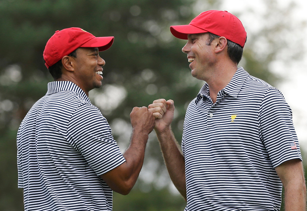 . United States team player Tiger Woods, left, and team player Matt Kuchar fist bump after Kuchar made a birdie putt on the fourth hole during a foursome match at the Presidents Cup golf tournament at Muirfield Village Golf Club, Friday, Oct. 4, 2013, in Dublin, Ohio. (AP Photo/Darron Cummings)