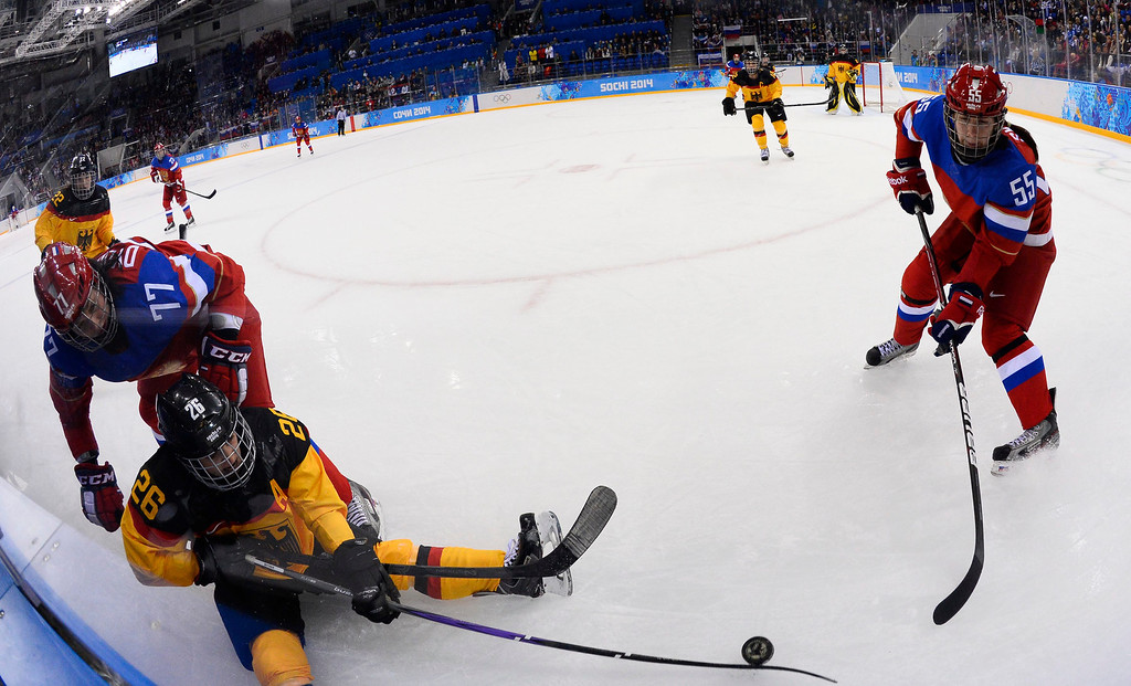 . Monika Bittner (C) of Germany knocks the puck away from Inna Dyubanok (L) and Galina Skiba (R) of Russia in the first period during their match in the Ice Hockey tournament at the Sochi 2014 Olympic Games in Sochi, Russia, 09 February 2014.  EPA/LARRY W. SMITH