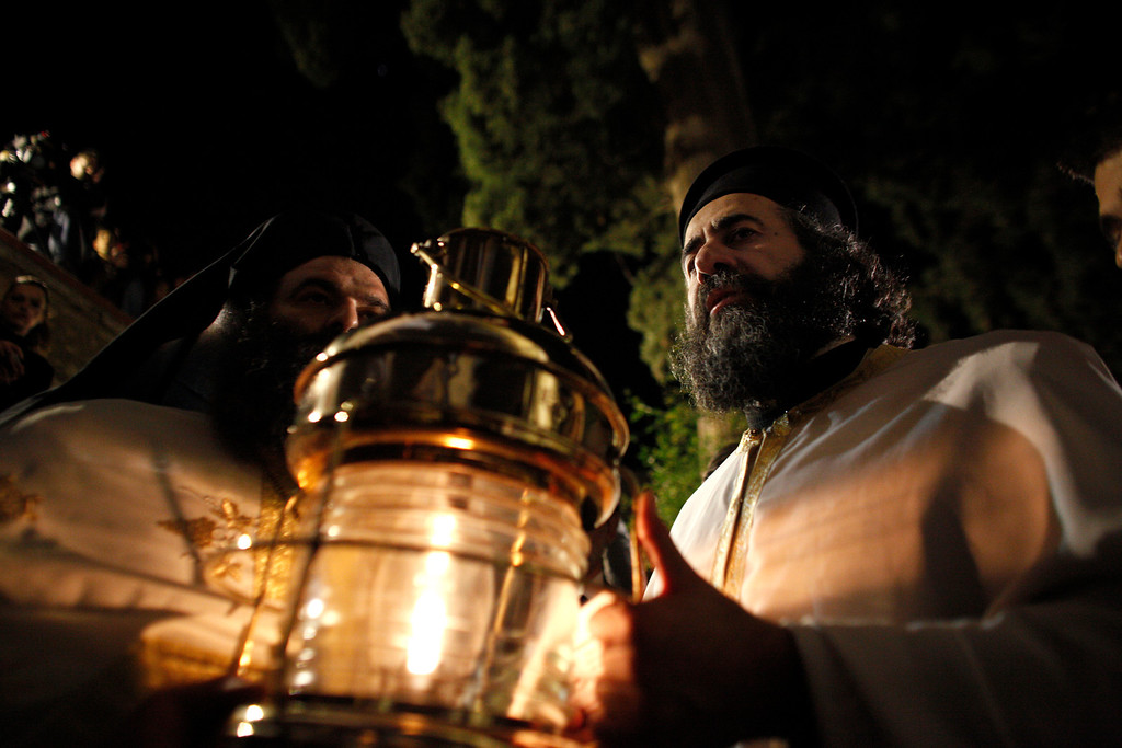 . Greek Orthodox priests carry the Holy Fire during an Easter Mass at the church of Agii Anargyri in Athens, late Saturday, April 19, 2014. The Holy Fire is brought in Greece every year from the church of the Holy Sepulcher in Jerusalem, traditionally believed to be the burial site of Jesus Christ . (AP Photo/Kostas Tsironis)