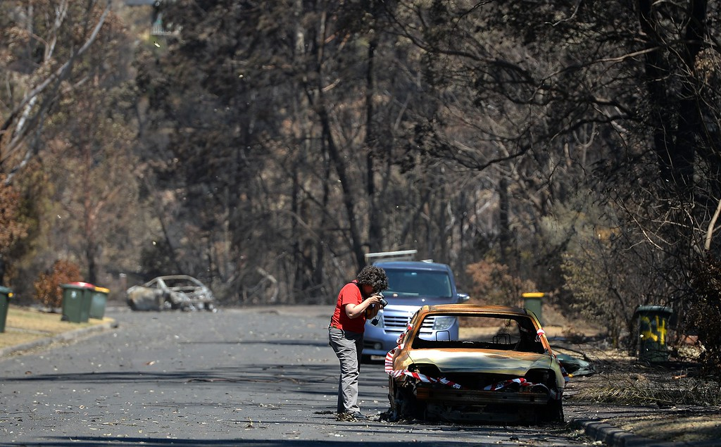 . A woman takes pictures of a car burnt out by recent bush fires in Springwood in the Blue Mountains on October 23, 2013.  Firefighters in Australia battled hot, dry winds and soaring temperatures as new blazes began breaking out in a week-long bushfire disaster that shows no signs of easing.  AFP PHOTO / Saeed KHAN/AFP/Getty Images