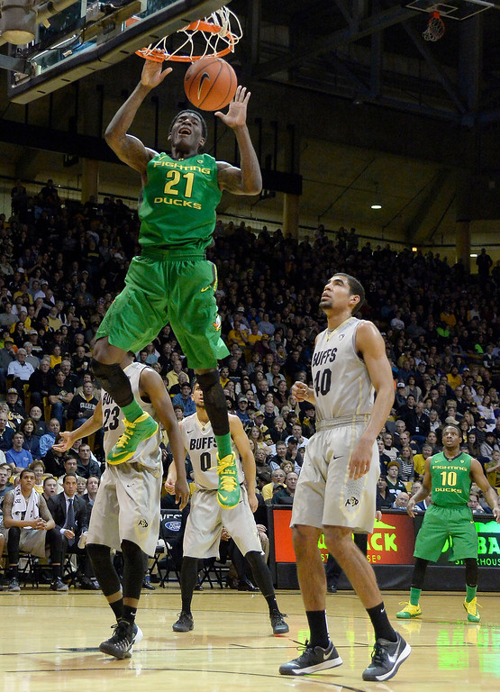 . Oregon Ducks guard Damyean Dotson (21) gets an easy dunk as Colorado Buffaloes forward Josh Scott (40) looks on during the first half January 5, 2014 at Coors Events Center. (Photo by John Leyba/The Denver Post)