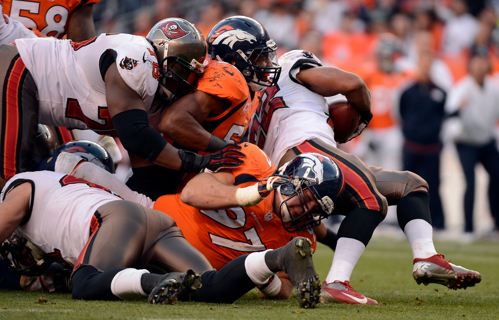 . Tampa Bay Buccaneers running back Doug Martin #22 gets stopped by Denver Broncos outside linebacker Wesley Woodyard #52 during the third quarter.  The Denver Broncos vs The Tampa Bay Buccaneers at Sports Authority Field Sunday December 2, 2012. John Leyba, The Denver Post