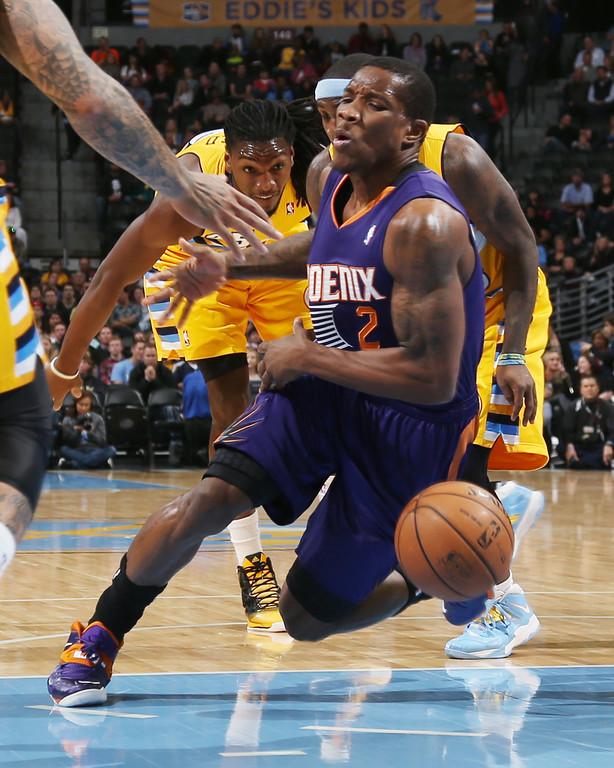 . Phoenix Suns guard Eric Bledsoe, front, reacts as he is fouled while driving the lane by Denver Nuggets guard Ty Lawson, center, as forward Kenneth Faried trails the play in the first quarter of an NBA basketball game in Denver on Friday, Dec. 20, 2013. (AP Photo/David Zalubowski)