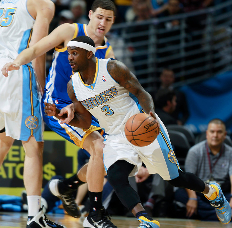 . Denver Nuggets guard Ty Lawson (3) works ball inside past Golden State Warriors guard Klay Thompson in the first quarter of an NBA basketball game in Denver, Monday, Dec. 23, 2013. (AP Photo/David Zalubowski)