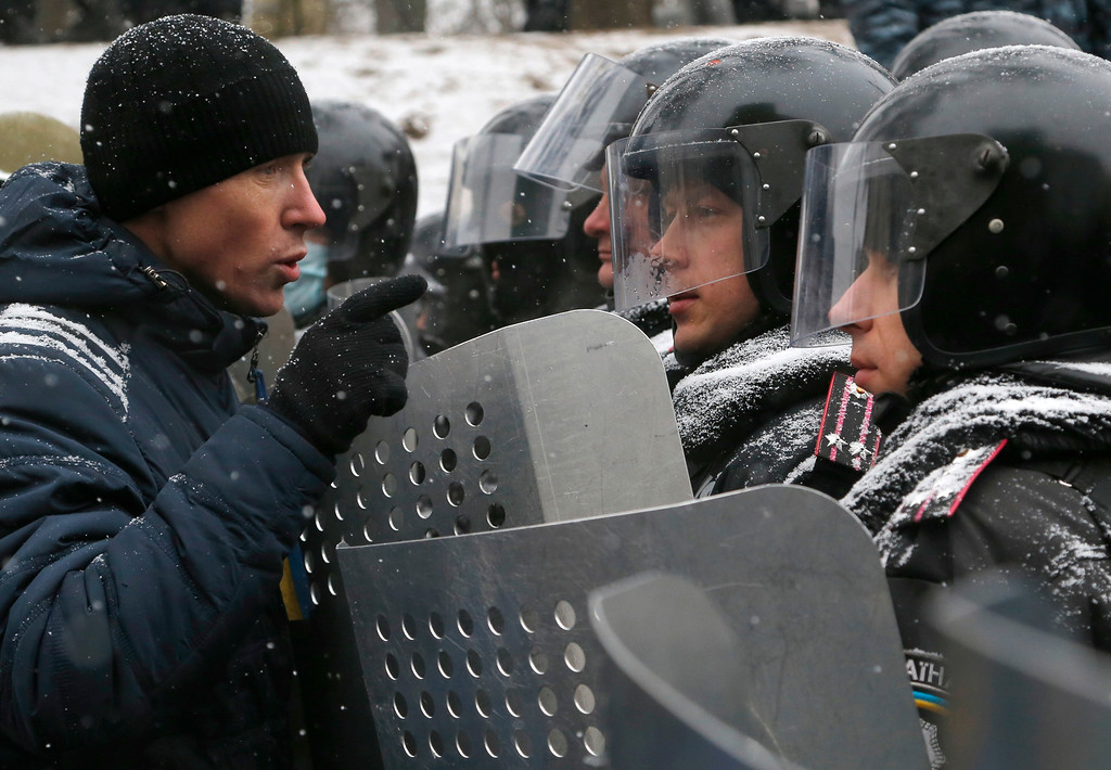 . A pro-European Union activist speaks to police officers as they block a street in central Kiev, Ukraine,Tuesday, Jan. 21, 2014.  (AP Photo/Sergei Grits)