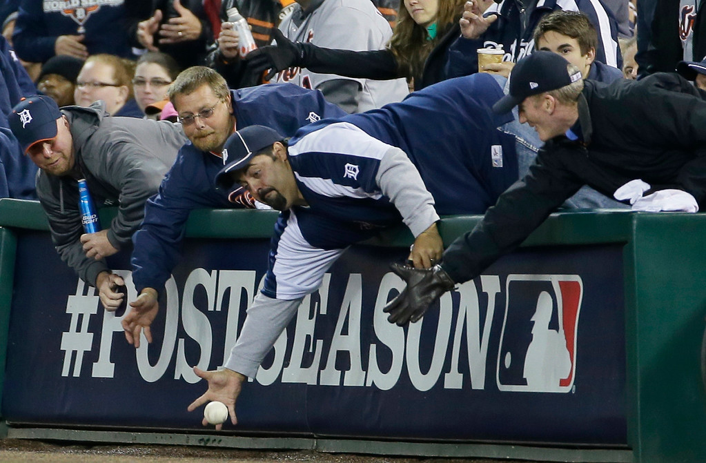 . Fans reach for a foul ball hit by Boston Red Sox\'s Stephen Drew in the second inning during Game 5 of the American League baseball championship series against the Detroit Tigers, Thursday, Oct. 17, 2013, in Detroit. (AP Photo/Matt Slocum)