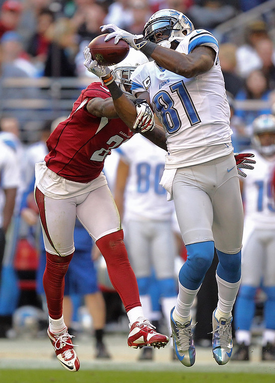. Detroit Lions wide receiver Calvin Johnson (81) makes a catch as Arizona Cardinals cornerback Patrick Peterson (21) defends during the first half of an NFL football game on Sunday, Dec. 16, 2012, in Glendale, Ariz. (AP Photo/Paul Connors)