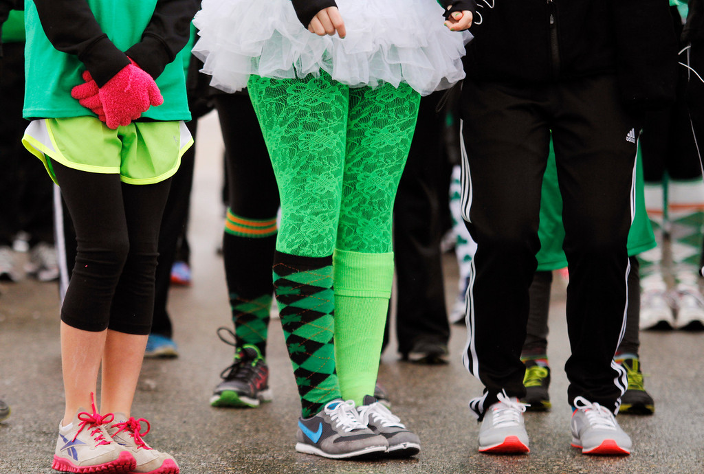 . Spectators stand wearing St. Patrick\'s Day decor during the Shamrock Shuffle 5K Race/Walk in Hartford, Wis.  on Saturday, March 16, 2013. Proceeds from the race benefited the Hartford Union Varsity Club.  (AP Photo/The Daily News, John Ehlke)