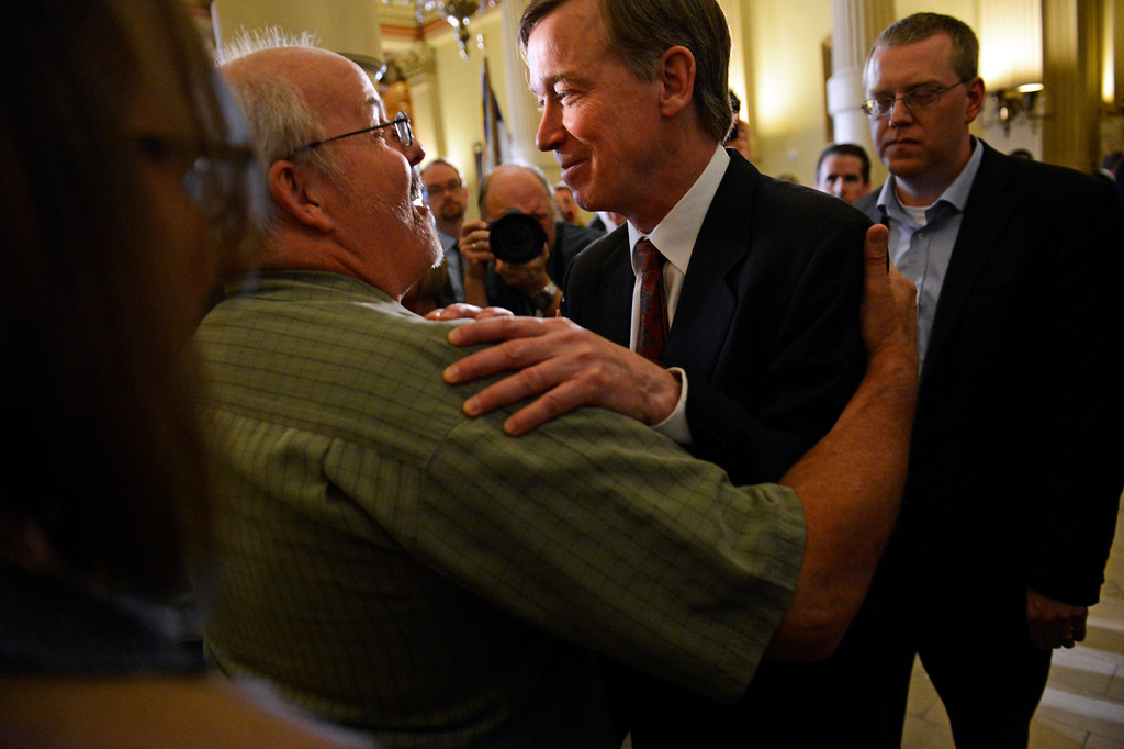 . DENVER, CO. - MARCH 20: Tom Sullivan, left, who\'s son was killed in the Aurora theater shooting, hugs Colorado Governor John Hickenlooper, after a press conference at the Colorado State Capitol, March, 20, 2013. Hickenlooper earlier signing three gun control measures making stricter gun laws in Colorado. (Photo By RJ Sangosti/The Denver Post)