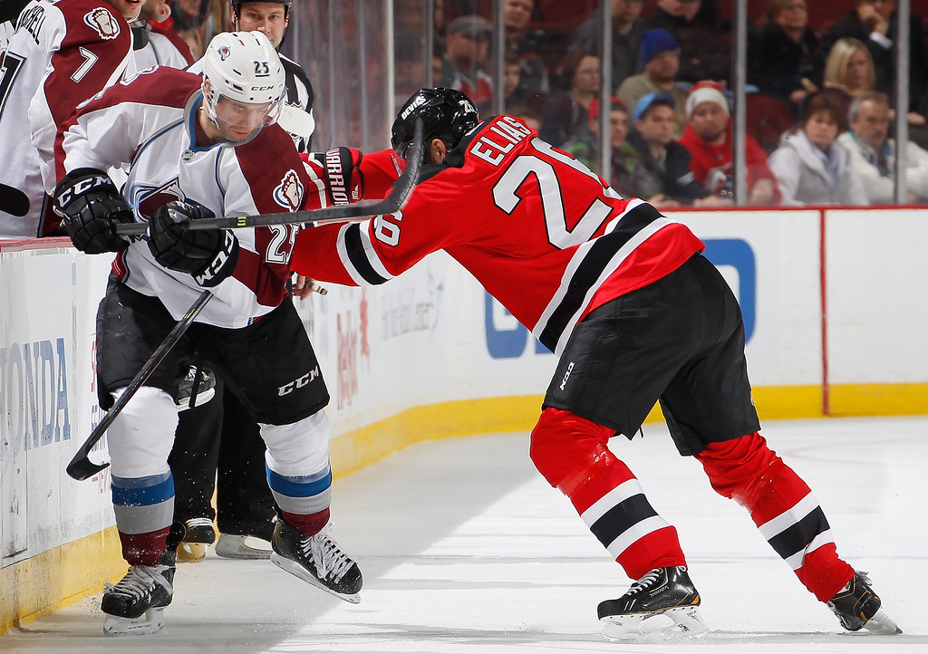 . Patrik Elias #26 of the New Jersey Devils checks Colorado Avalanche center Maxime Talbot #25 during the second period in an NHL hockey game at Prudential Center on February 3, 2014 in Newark, New Jersey.  Colorado won 2-1 in overtime.  (Photo by Paul Bereswill/Getty Images)