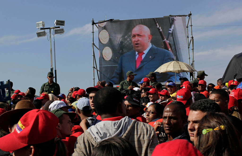 . A screen showing a video image of Venezuela\'s President Hugo Chavez plays in front of the site where Chavez\'s funeral ceremony will take place as people gather outside the military academy in Caracas, Venezuela, Friday, March 8, 2013. (AP Photo/Rodrigo Abd)